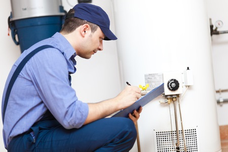 crouching plumber with blue hat and clipboard looking at water heater
